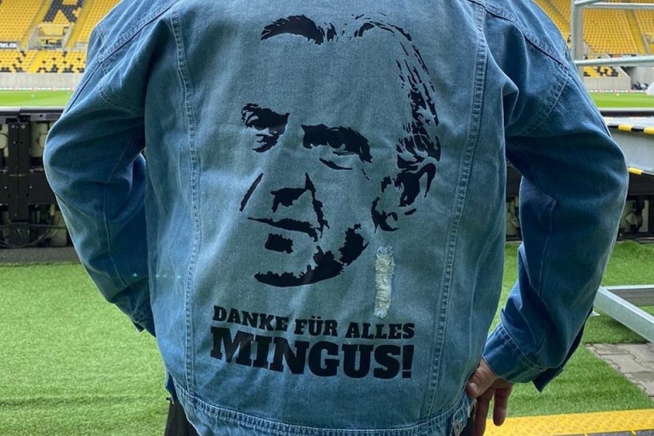 Die Mannschaft verabschiedet sich auf ihre Weise von Sportchef Minge, dessen Jeansjeack in Fußball-Dresden mittlerweile Kult-Charakter hat. Diese Jeansjacke mit Aufschrift tragen die Spieler bei der Erwärmung.