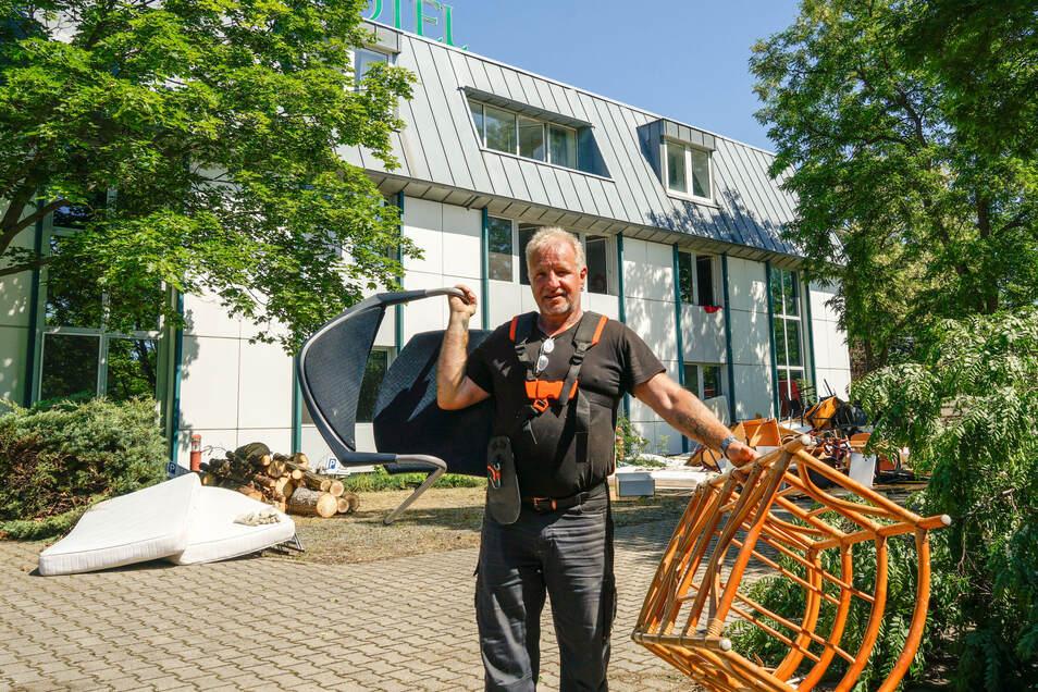Ingolf Brahmann trägt alte Möbel aus dem einstigen Spreehotel zum Sperrmüllcontainer. Noch bis zum Ende der Woche wird hier geräumt - wann es danach weitergeht, ist aber noch offen.
