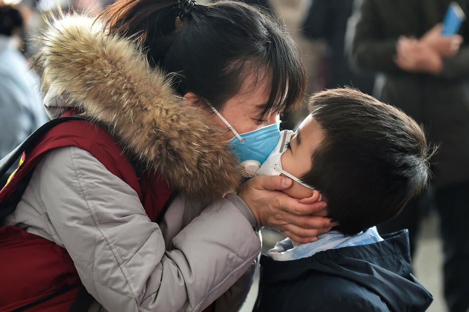 Eine Mitarbeiterin eines Ärzteteams küsst ihren Sohn, bevor sie vom Flughafen Yaoqiang aus in die Provinz Hubei aufbricht. Die 12. Gruppe von 170 medizinischen Mitarbeitern aus Shandong fliegt nach Hubei, um dort bei der Kontrolle des Coronavirus zu helf