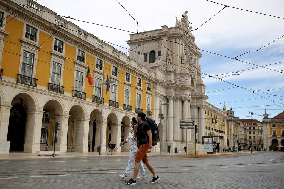 Menschen mit Mund-Nasen-Schutz spazieren in der Innenstadt von Lissabon.