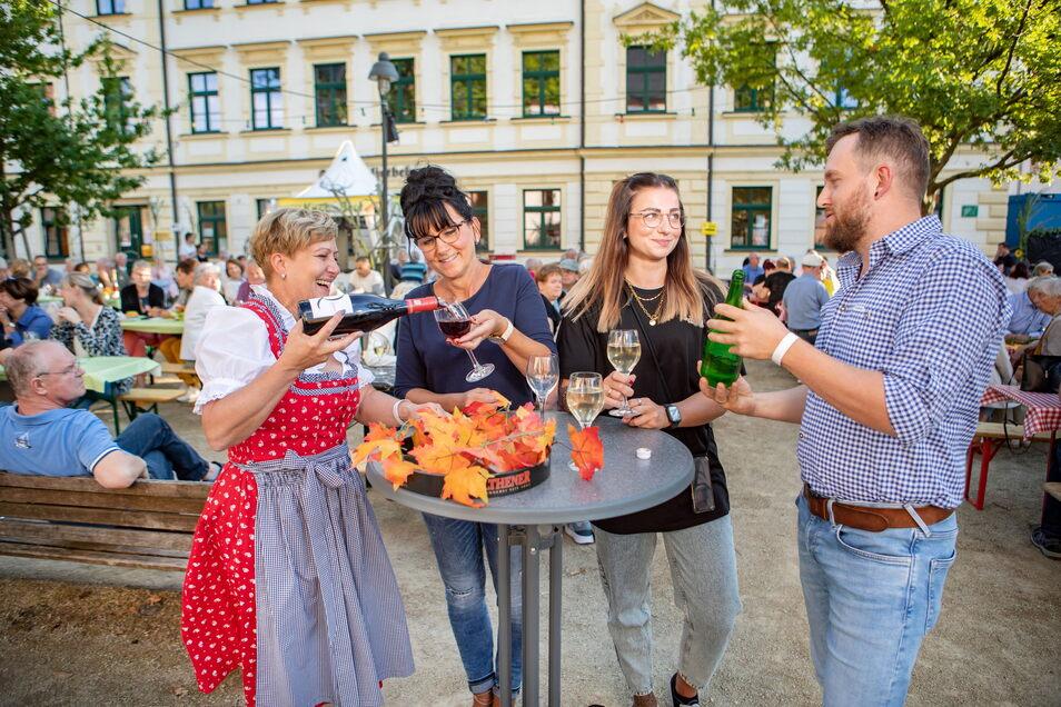 Silke Stiehler (2. von links) und ihre Tochter Liz lassen sich von Corinna Börnert (links) und Tobias Kühn  Wein einschenken.