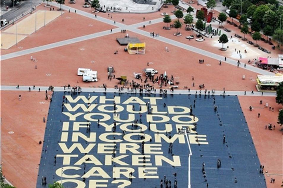 """In riesigen Lettern stand auf dem Poster aus Lastwagenplanen: """"What would you do if your income were taken care of?"""" (""""Was würdest du tun, wenn für dein Einkommen gesorgt wäre?"""")"""