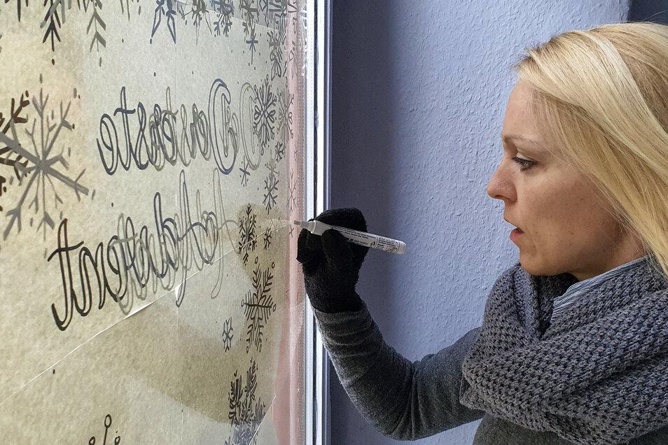 Maria Weber bringt mit Kreidestiften an allen Stationen des Adventskalenders die jeweilige Türchen-Nummer an.