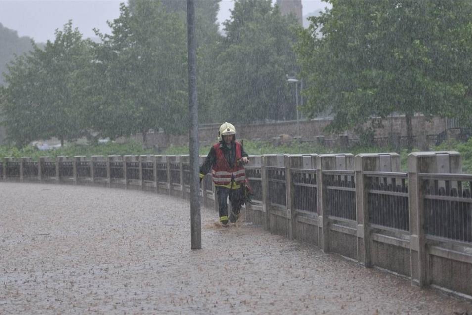 Ein Feuerwehrmann kämpft sich durch das überflutete Triebischtal in Meißen. Starkregen hatte hier einen Erdrutsch ausgelöst.
