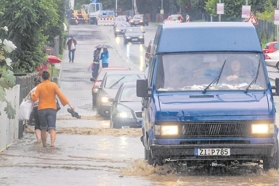 Auf der Löbauer Straße mussten sich Fußgänger wie Autofahrer durch die Wassermassen kämpfen. Die Flut wurde zum Medienereignis. Nicht nur Zeitungen und Agenturen waren vor Ort, Radio- und TV-Reporter berichteten live.