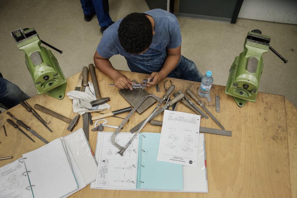 Ein Lehrling aus Eritrea sitzt an seiner Werkbank und misst ein Werkstück nach.