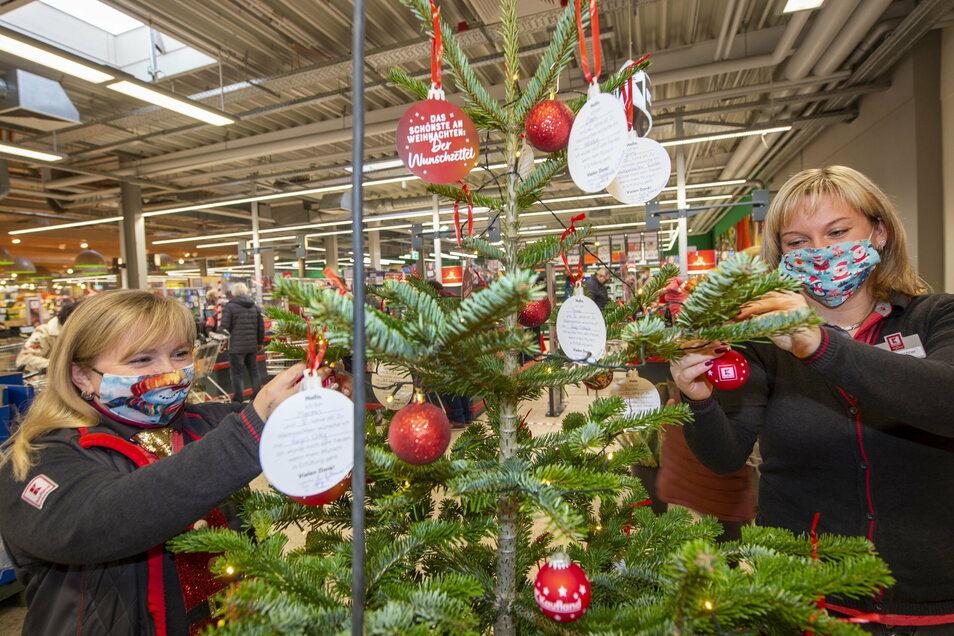 Susann Lottenburger (li.) und Jenny Leuschner hängen im Großenhainer Kaufland Weihnachtskugeln an den Baum. Jede Kugel wartet nun auf einen Käufer, damit die Wünsche der Kinder wahr werden.