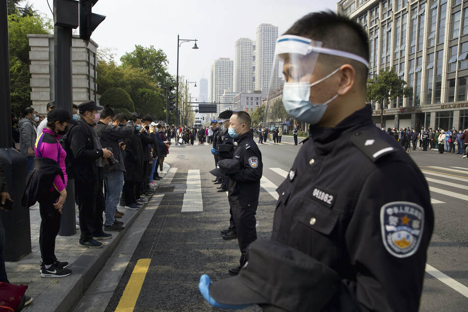 Einwohner und Polizisten gedenken in Wuhan mit drei Schweigeminuten der Toten durch das neue Coronavirus - laut Statistik fielen in der Stadt mehr als 2.500 Menschen dem Virus zum Opfer.