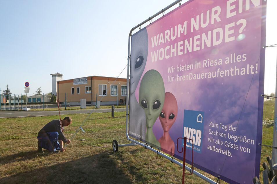 Michael Löwe von der Firma RDL installiert ein Plakat auf dem Großparkplatz am Flugplatz Göhlis. Die anderen Parkplätze sind in Groptitz und Röderau-Süd.