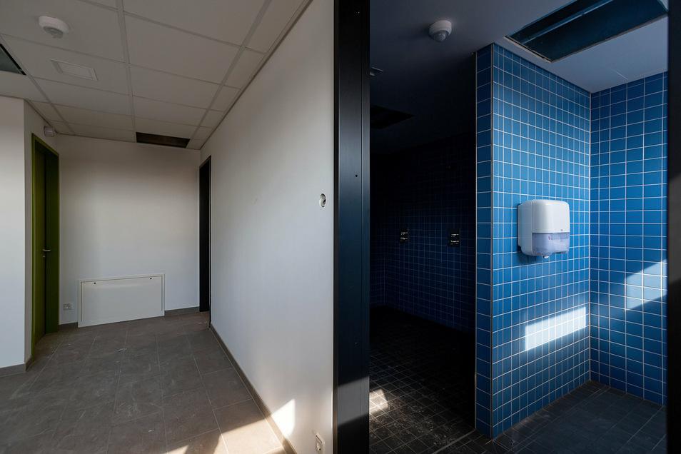 Insgesamt gibt es sechs Garderoben mit je drei Duschen, drei Waschbecken und einer Toilette in der neuen Sporthalle. Hier werden noch Hakenleisten angebracht und Bänke aufgestellt.