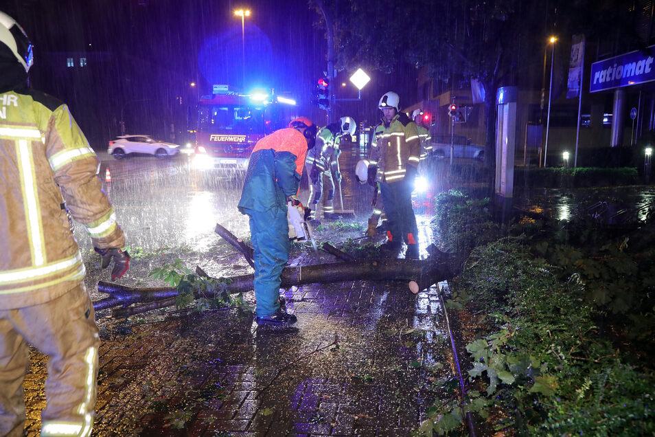 Feuerwehrmänner beräumen an der Nossener Brücke im strömenden Regen die Fahrbahn.