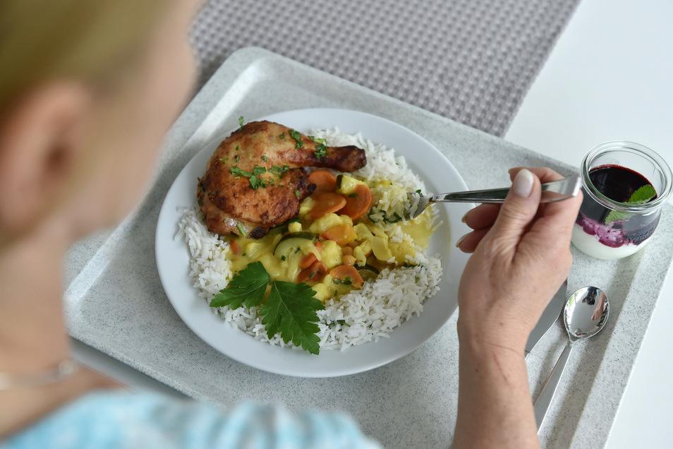 Eine Frau isst in einer Kantine zum Mittag.