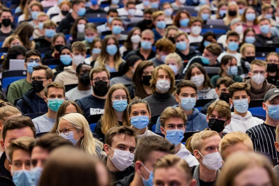 Studierende tragen Maske, während sie dicht nebeneinander bei der Vorlesung sitzen. An den Universitäten haben das erste Mal seit Beginn der Corona-Pandemie die Vorlesungen im Wintersemester 2021/22 in Präsenz unter 3G-Bedingungen begonnen.