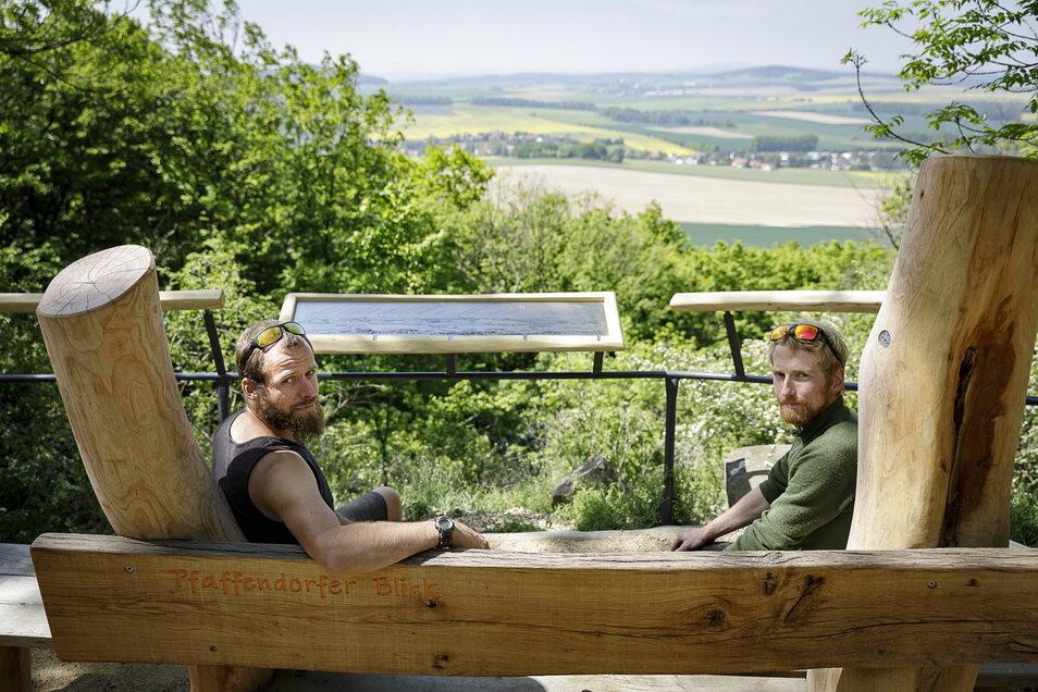 """Christoph Kretzschmar (links) und Philipp Weise von der Firma Holzgestalten aus Ostritz sitzen vor der neuen Panorama-Tafel am Aussichtspunkt """"Pfaffendorfer Blick"""" auf der Landeskrone."""