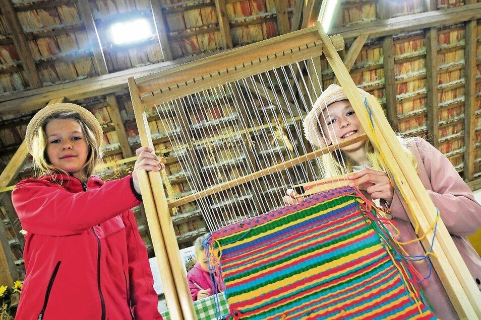 """Die Geschwister Sarah Marie (11) und Hanna Mira (8) (v.r.) sind Experten am Webrahmen. Unter der Leitung von Ralph-Torsten Lincke nahm das Museum Unterwegs mit seiner Aktion """"Wie Kinder früher spielten"""" an der Eröffnung teil."""