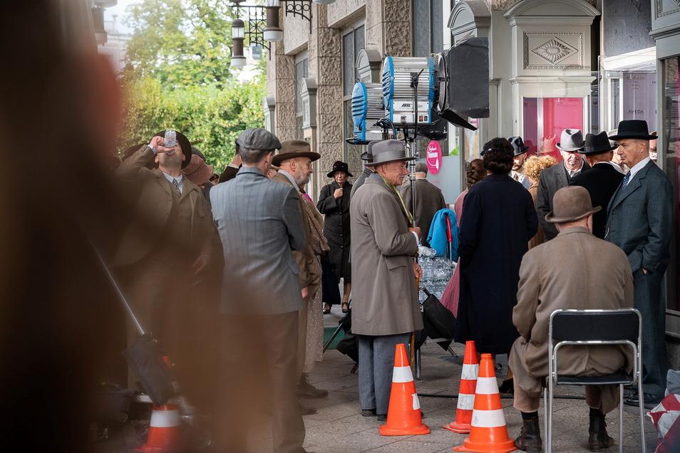 """Komparsen warten auf ihren Einsatz vorm Kaufhaus am Demianiplatz für die Dreharbeiten der Serie """"Torstraße 1""""."""
