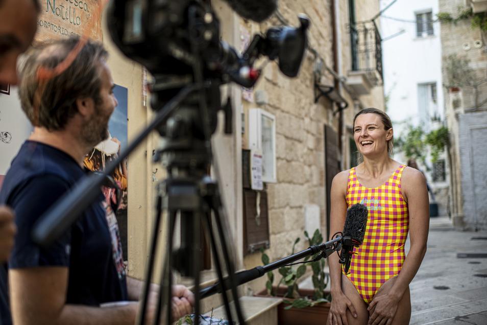 Am Rande der Wettkämpfe gibt Iris Schmidbauer Interviews, erzählt, wie es sich anfühlt, drei Sekunden durch die Luft zu wirbeln.