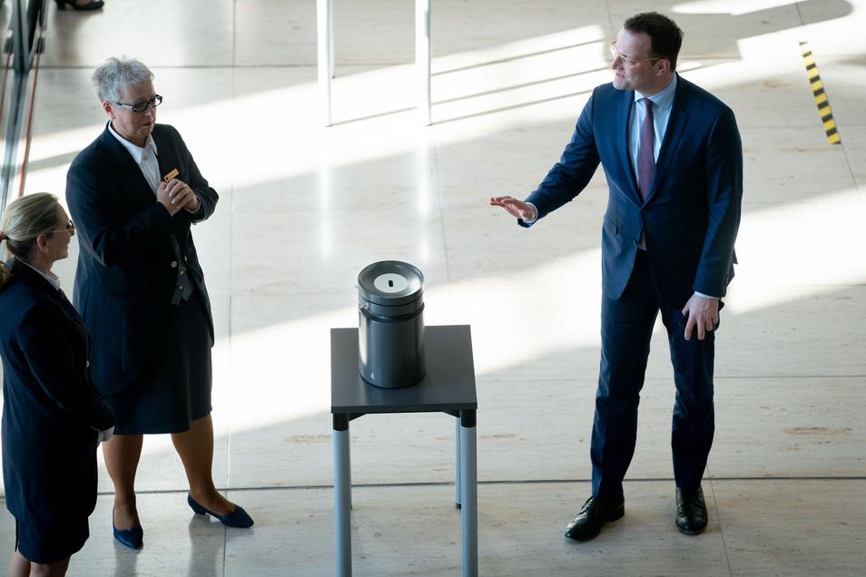 Jens Spahn (CDU), Bundesminister für Gesundheit, spricht nach Abgabe seiner Stimmkarte mit Mitarbeiterinnen des Bundestages.