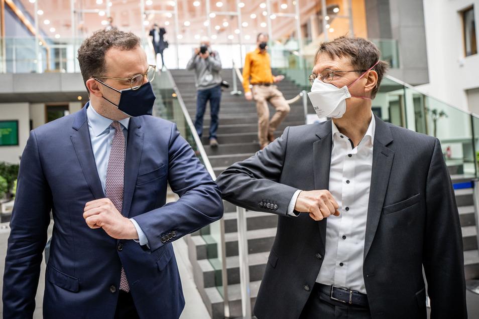 Jens Spahn (CDU, l), Bundesminister für Gesundheit, verabschiedet sich mit einem Ellenbogen-Kick von Karl Lauterbach, SPD-Gesundheitsexperte.