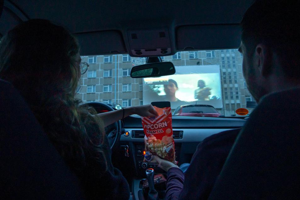 """Popcorn hinterm Lenkrad: Im Autokino auf dem Bautzener Flugplatz gab es am Freitag den Film """"Parasite"""" zu sehen. Etwa 40 Autos hatten dafür vor der Leinwand eingeparkt."""