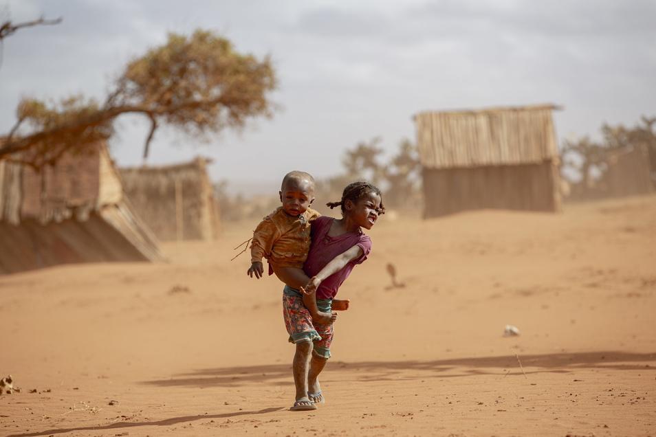 Ein Mädchen trägt ein kleines Kind im Süden Madagaskars durch den Staub.