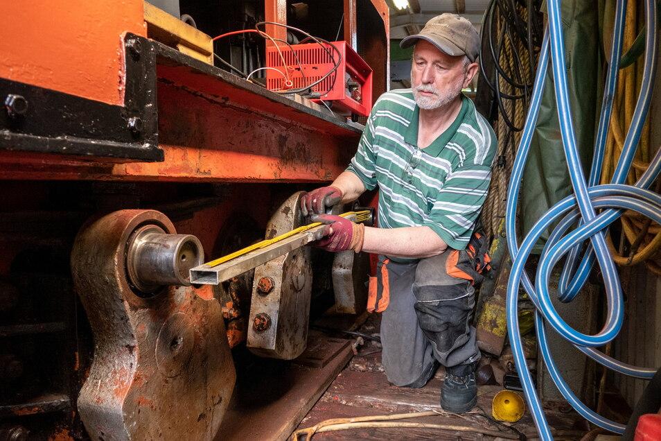 Vereinschef Hans-Rainer Fischer an der noch nicht wieder fahrbereiten Lok. Teile davon sind zur Reparatur.