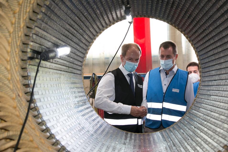Geschäftsführer Tomas Götze (links) und der FDP-Bundestagsabgeordnete Torsten Herbst stehen an einem Elektromotor, der bei Partzsch überholt wird.