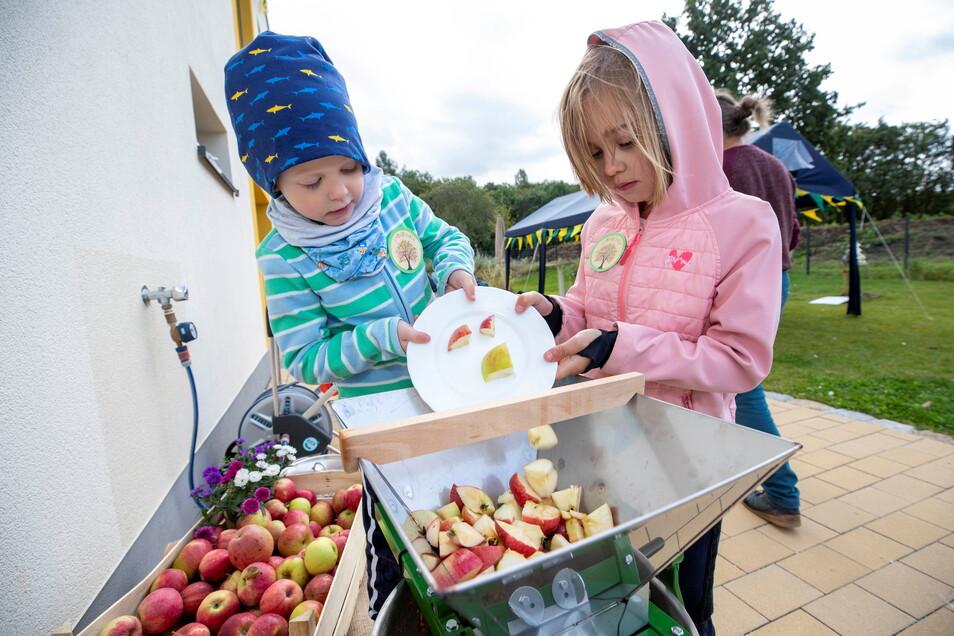 Hier wird selbst Limo gemacht: Der vierjährige Felix (l.) und die sechsjährige Frieda schütten kleine Apfelstücken in einen Zerkleinerer, die dann zu Apfelsaft in einer Saftpresse werden.