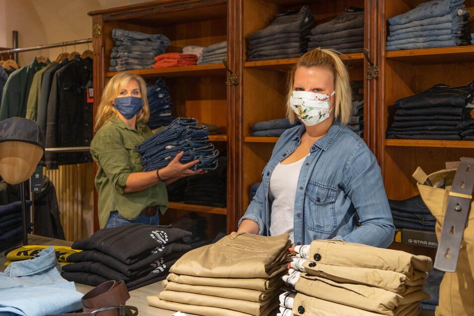 Sie müssen Mundschutz tragen, können aber endlich wieder arbeiten: Silvana Herrmann (l.) und Nancy Wollmann sortieren im Geschäft Atrium an der Bautzener Reichenstraße Ware ein.