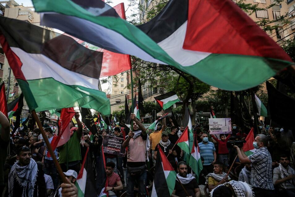 Anhänger der Hisbollah schwenken in Beirut palästinensische Fahnen und halten Plakate während einer Kundgebung, um Solidarität mit dem palästinensischen Volk auszudrücken.