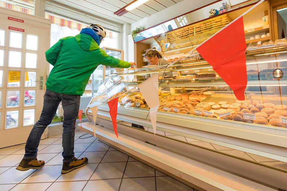 Eine Absperrleine mit roten und weißen Wimpeln sorgt für Abstand zwischen Verkäuferin und Kunden.