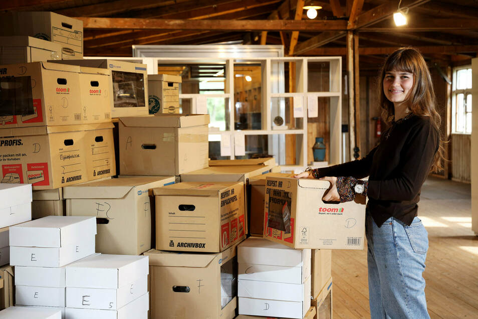 Luise Kröner absolviert gerade ihr Freiwilliges Soziales Jahr in der Gedenkstätte Ehrenhain Zeithain. Die Kisten enthalten Fundstücke vom Friedhof bei Jacobsthal.