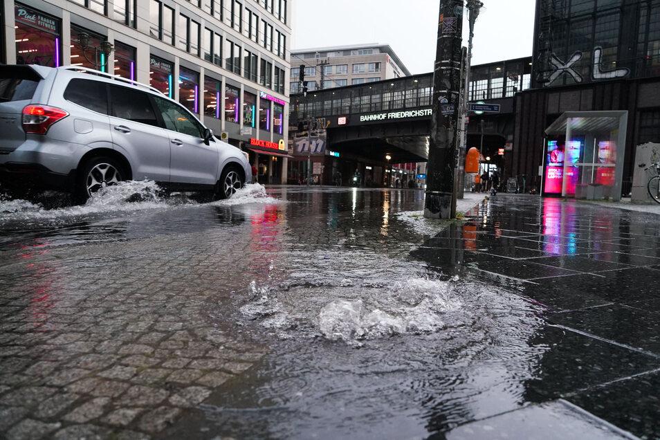 Nach einem starken Regenschauer quillt Wasser aus der Kanalisation auf der Friedrichstraße in Berlin-Mitte.