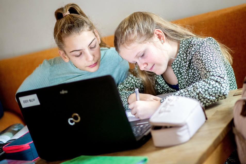 Die Schwestern Milla (l, 7. Klasse) und Juli (5. Klasse) sitzen am Esstisch im Wohnzimmer ihrer Familie und bearbeiten mithilfe eines Laptops Aufgaben für die Schule.