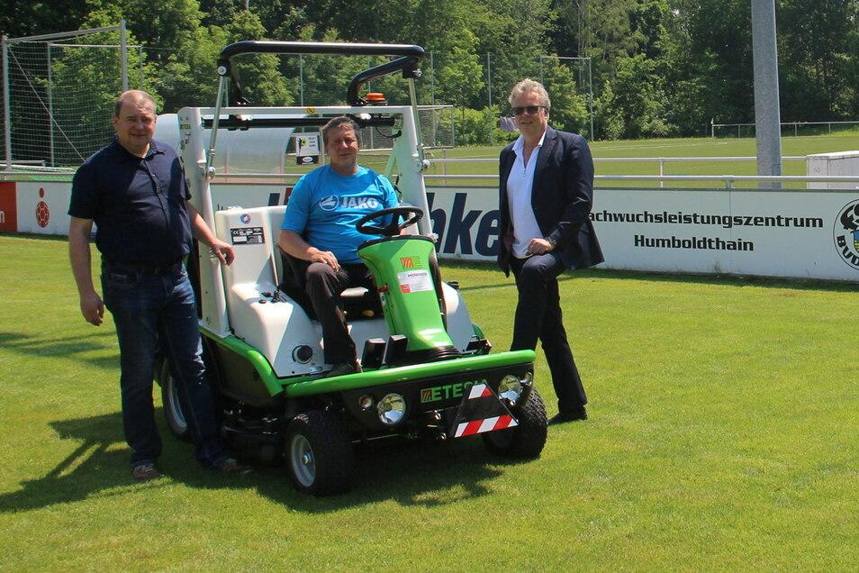Ein neuer Traktor für den Fußballverein Budissa in Bautzen. Die Firma von Jürgen Drews (r.), Geschäftsführer von Hentschke Bau, spendete das Gerät. Darüber freuen sich Andreas Vogel (Mitte), Objektverantwortlicher und Holger Schmidt von der Geschä