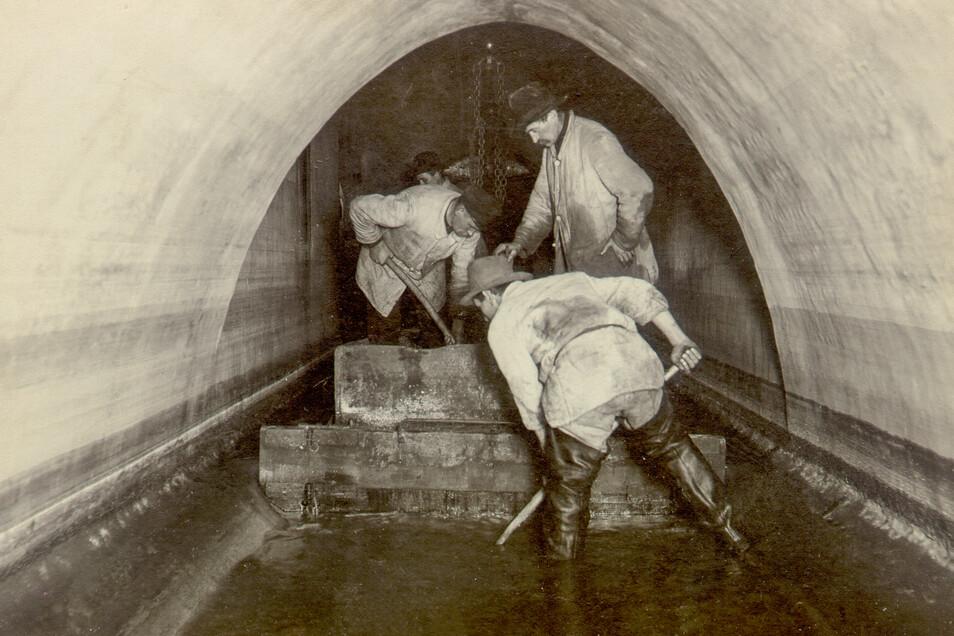 Schon vor 100 Jahren wurden die Kanäle regelmäßig gereinigt. Hier sind Kanalarbeiter dabei, den Boden der großen Röhre mit einem Kahn zu reinigen. Dabei handelt es sich allerdigns um ein altes Verfahren, das durch den Kanalreinigungswagen abgelöst wurde.