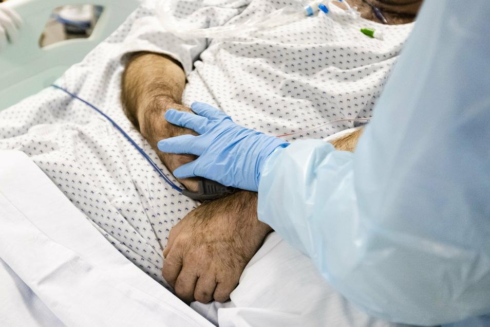 Ein letztes Mal über die Hand streicheln: Für die Dresdner Krankenschwester Anika Fried ist das ein Ritual, um sich von ihren verstorbenen Corona-Patienten zu verabschieden. © dpa/Frank Molter (Symbolfoto)