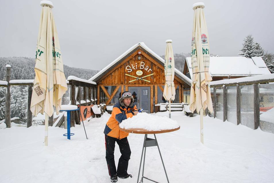 Alexander Richter, Betreiber des Skigebietes Holzhau steht vor der geschlossenen Ski Bar an seinem ungenutzten Skihang.