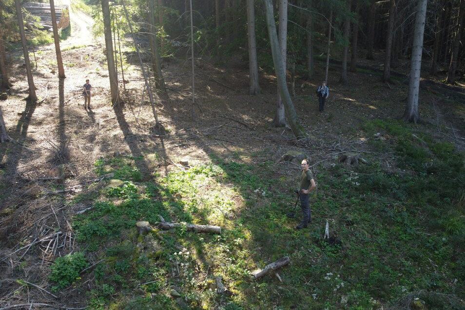 Mitarbeiter von: Archaeoforest stehen hier an einem Plateau, auf dem früher ein Kohlenmeiler betrieben wurde. Ihre Position zeigt die Ausmaße der Anlage.