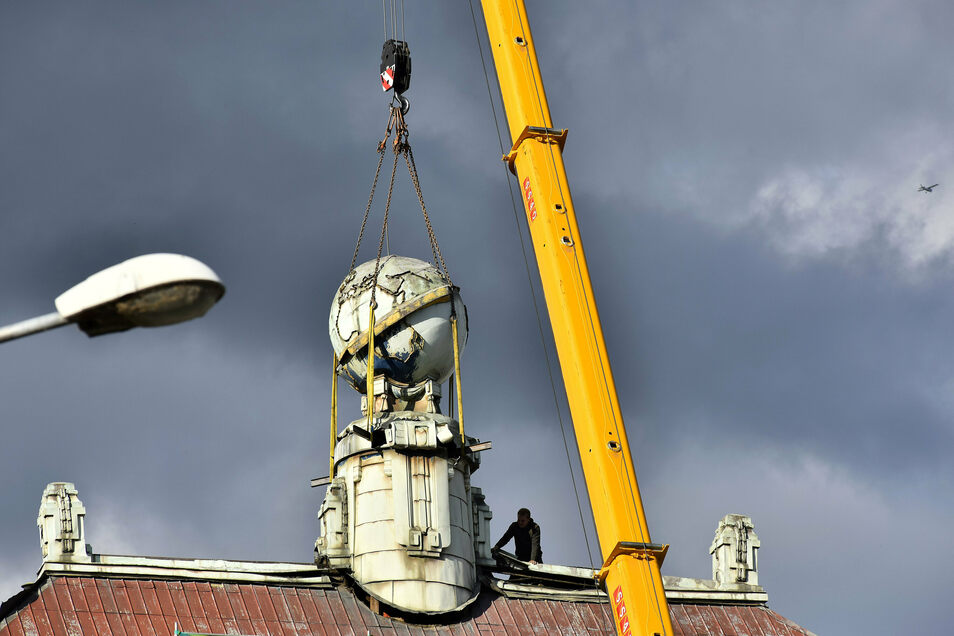 Mitarbeiter der Baufirma lassen den Globus mittels Kran zur Straße hinunter.