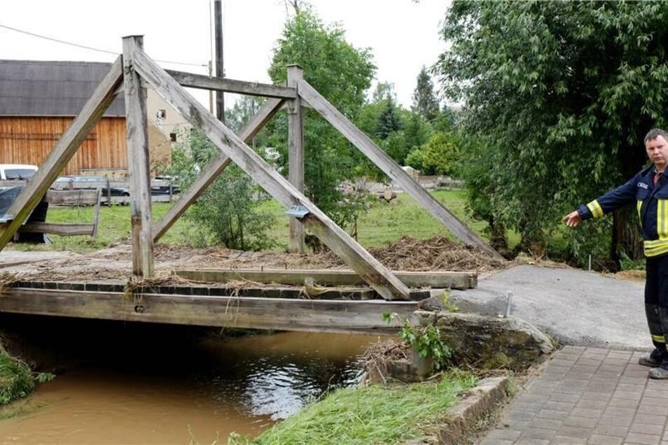 Eine Brücke in Ziegenhain wurde vom Wasser um einen halben Meter verrückt, wie Ortswehrleiter Thiel zeigt.
