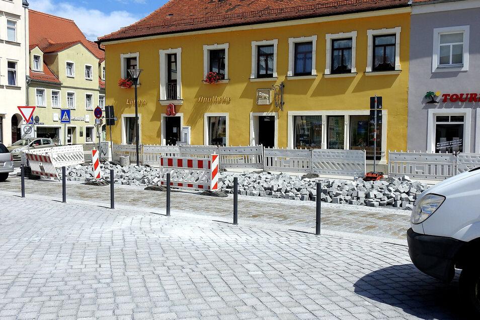 In den vergangenen Wochen wurde an verschiedenen Stellen am neu verlegten Pflaster des Radeburger Marktes gewerkelt. Am Montag früh ist das der Parkflächen vor der Apotheke nun sogar wieder ganz rausgeholt worden.