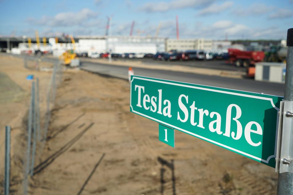 """Blick auf das Straßenschild """"Tesla Straße 1"""" vor der Baustelle der Tesla-Fabrik."""