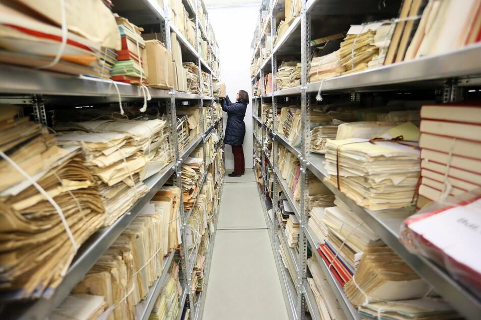 Eine Mitarbeiterin steht im Stasi-Archiv zwischen Regalen.