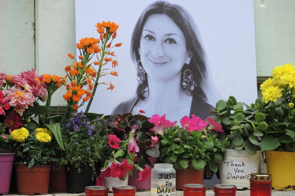 Kerzen und Blumen stehen im Gedenken vor einem Foto der ermordeten maltesischen Journalistin Daphne Caruana Galizia vor dem Justizpalast.