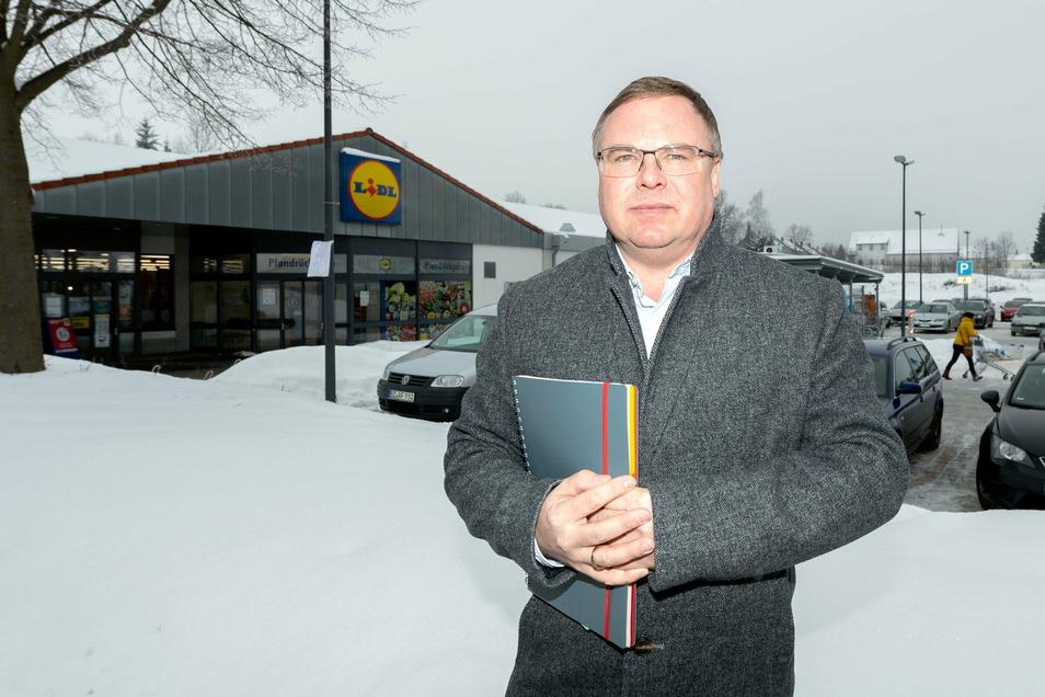 Neukirchs Bürgermeister Jens Zeiler freut sich, dass es endlich losgeht mit dem Lidl-Neubau. Der soll neben dem Parkplatz (hinten im Bild) entstehen.