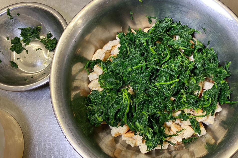 Brotwürfel mit blanchiertem Spinat und Zwiebeln locker vermengen.