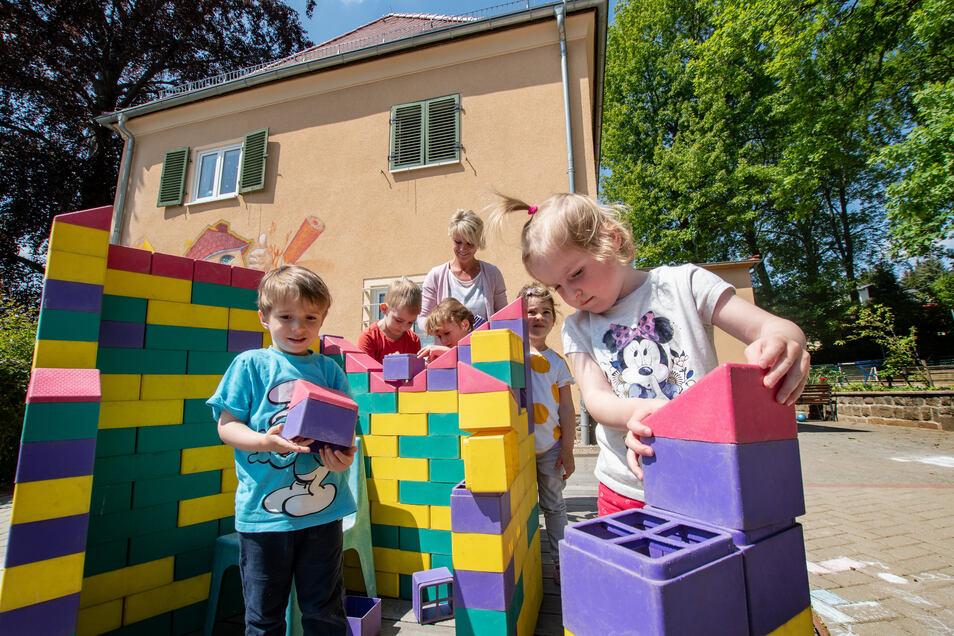 """Im """"Haus der kleinen Stifte Berta Semmig"""" in Döbeln spielen die Kinder im Außengelände in vier getrennten Bereichen. In einem bauen sie sich ein kleines buntes Häuschen."""