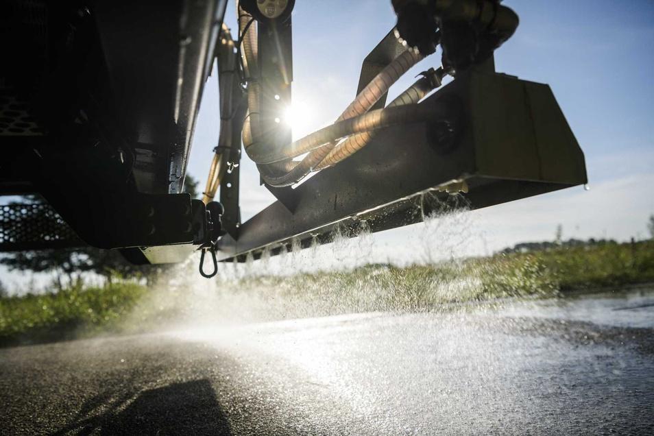 Salzwasser wird mit einem Streufahrzeug auf einer Straße in den Niederlanden ausgebracht.