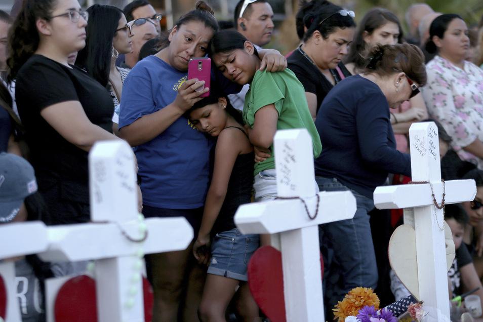 El Paso: Eine Mutter umarmt ihre Töchter, als sie ein provisorisches Denkmal für die Opfer des Massakers in El Paso besuchen.